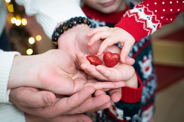 Vrouwelijke, baby- en mannelijke handen houden twee rode, glanzende harten vast. valentijnsdag, liefde, steun, vertrouwen.