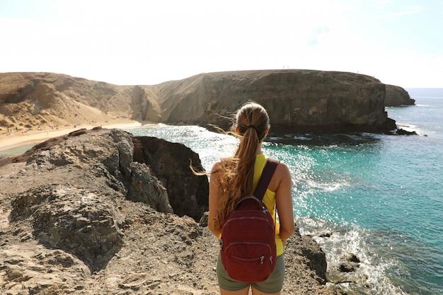 Vrouwelijke backpacker wandelaar op rotsen genieten van uitzicht op playa de papagayo strand in lanzarote, canarische eilanden