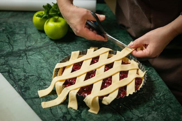 Vrouwelijke bakker bereidt kersen amerikaanse taart