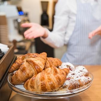 Vrouwelijke bakker die de gebakken croissants in de caketribune voorstelt