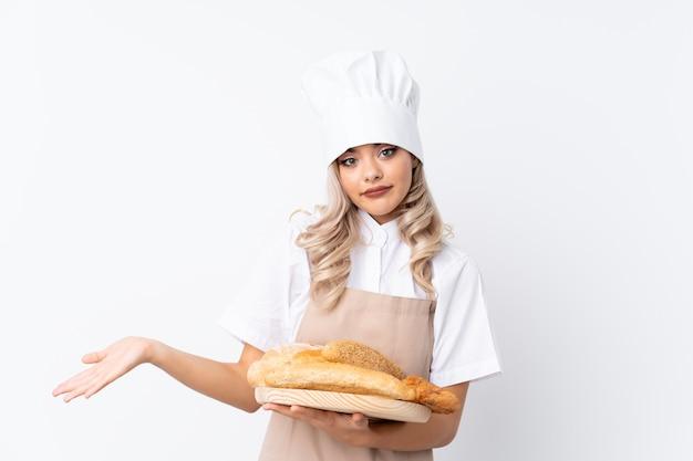 Vrouwelijke bakker die een tafel met verschillende broden houdt die wijzen naar de zijkanten die twijfels hebben