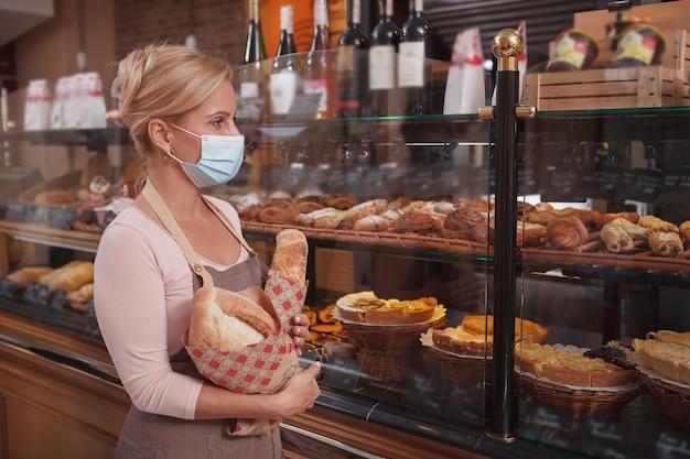 Vrouwelijke bakker die medisch gezichtsmasker draagt, die bij de bakkerijwinkel werkt, exemplaarruimte