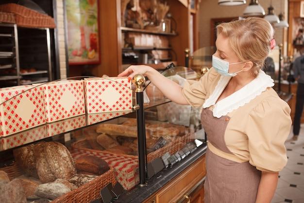 Vrouwelijke bakker die medisch gezichtsmasker draagt, die detailhandel in haar bakkerijwinkel organiseert
