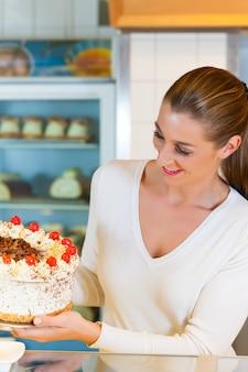 Vrouwelijke bakker of patissier met torte