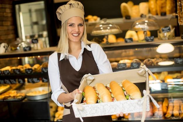 Vrouwelijke bakker poseren met verschillende soorten broodjes in de bakker winkel