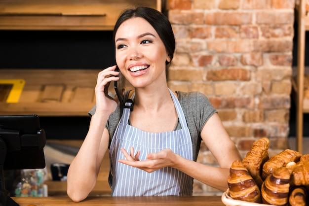 Vrouwelijke bakkerijeigenaar aan de balie met croissant praten op mobiele telefoon