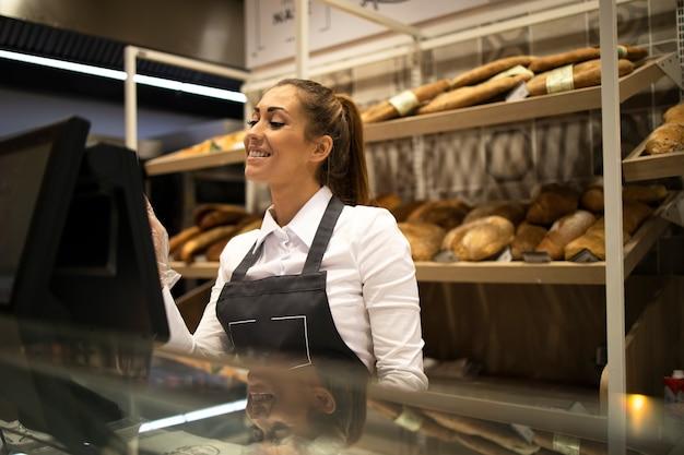 Vrouwelijke bakkersverkoper die aan computer werkt en brood in supermarkt verkoopt