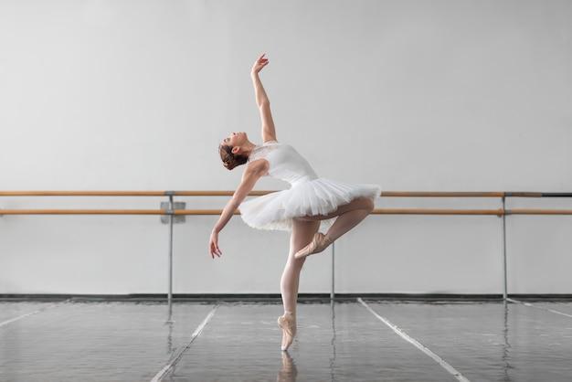 Vrouwelijke balletdanseres houden het rek in de klas