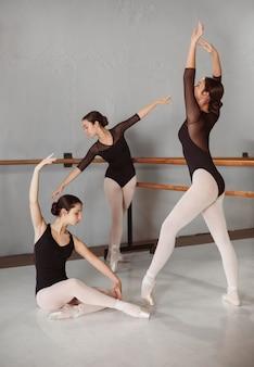 Vrouwelijke balletdansers trainen samen in pointe-schoenen en maillots