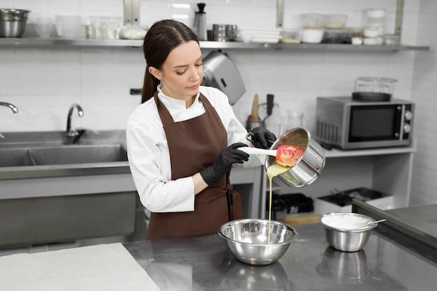 Vrouwelijke banketbakker giet gesmolten witte chocolade uit een pan in een moussekom.
