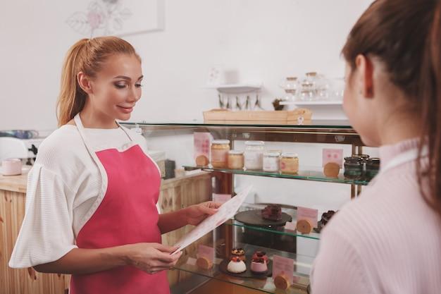 Vrouwelijke banketbakker in gesprek met collega die werkt bij rauwe veganistische zoetwaren winkel