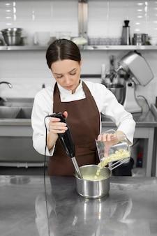 Vrouwelijke banketbakker maakt een spiegelglazuur met witte chocolade voor een cake met een blender.