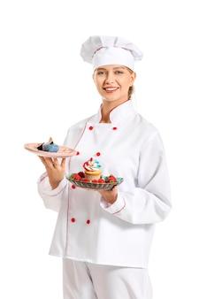 Vrouwelijke banketbakker met smakelijke desserts op wit