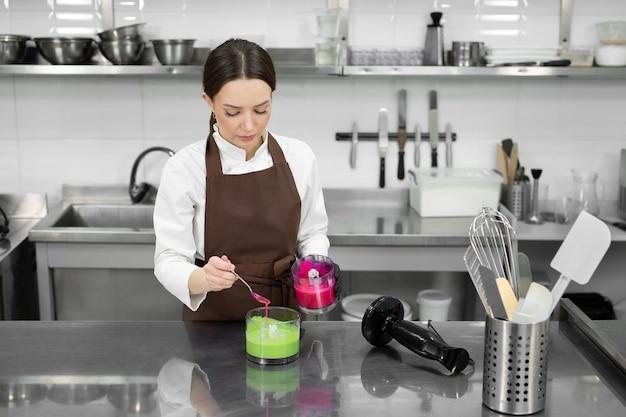 Vrouwelijke banketbakker schildert een spiegelglazuur in groen en roze in een professionele keuken.