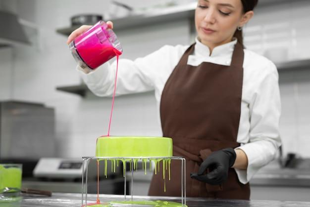 Vrouwelijke banketbakker versiert een moussecake met een spiegelglazuur.