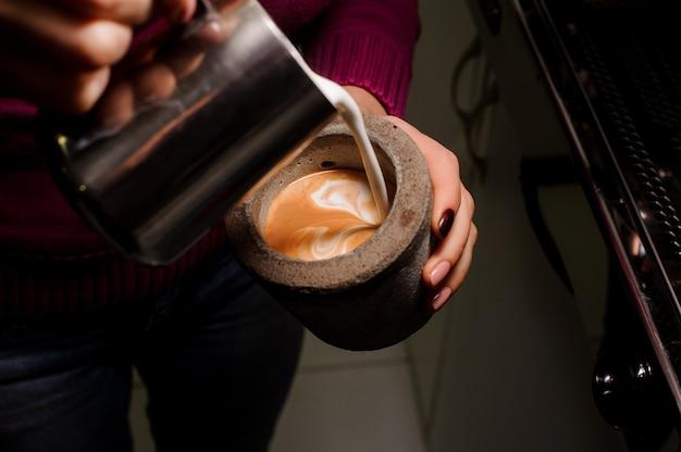 Vrouwelijke barista gietende melk in de concrete pot