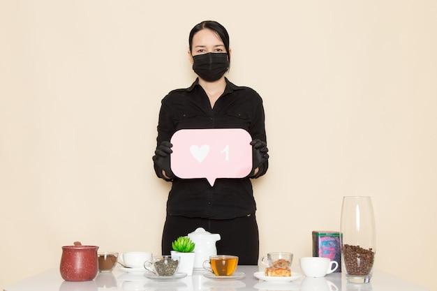Vrouwelijke barista in zwarte overhemd broek met koffie bruin gedroogde thee apparatuur ingrediënten in zwart steriel masker op de witte muur