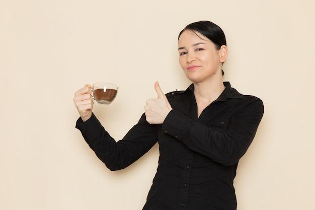 Vrouwelijke barista in zwarte overhemd broek met kop koffie op de witte muur