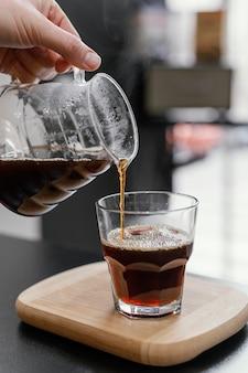 Vrouwelijke barista koffie gieten in transparant glas
