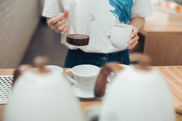 Vrouwelijke barista met glazen mok en kopje koffie