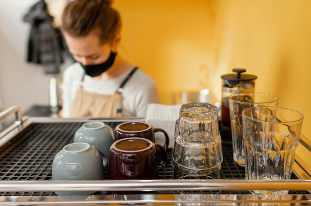 Vrouwelijke barista met masker dat in de coffeeshop werkt
