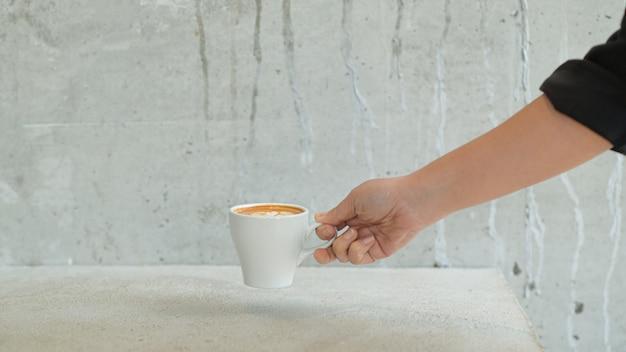Vrouwelijke barista plaatst een koffiekop op tafel om de klant te bedienen.