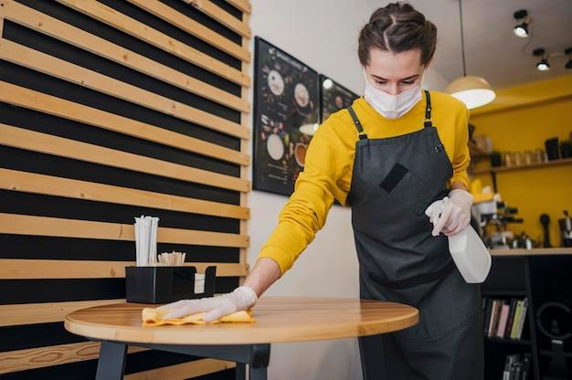 Vrouwelijke barista schoonmaak tafel terwijl het dragen van medische masker