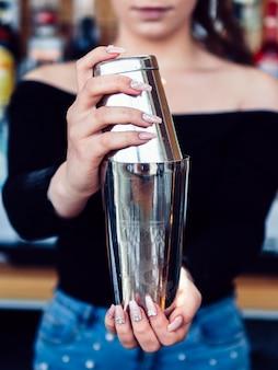 Vrouwelijke barman die drank in schudbeker voorbereidt
