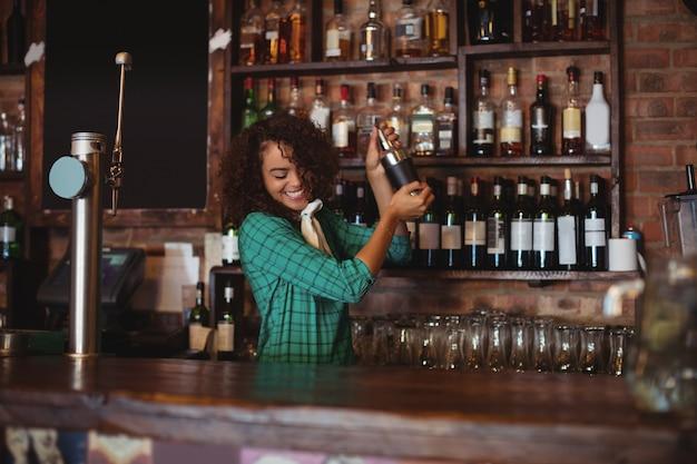 Vrouwelijke barman die een cocktaildrank in cocktailshaker mengt