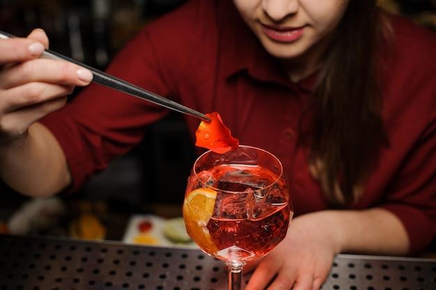 Vrouwelijke barman die een glas aperol-spuitcocktail verfraaien met rozenblaadjes