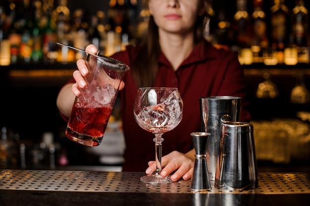 Vrouwelijke barman die zoete rode alcoholische drank gieten in een glas
