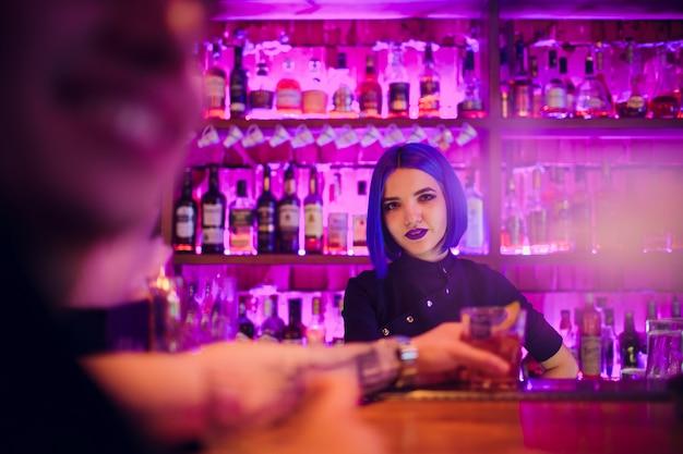 Vrouwelijke barman. meisje met blauw haar. cocktail maken in de nachtbar
