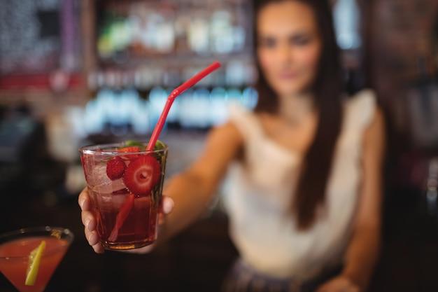 Vrouwelijke barman serveert een cocktaildrankje bij toog