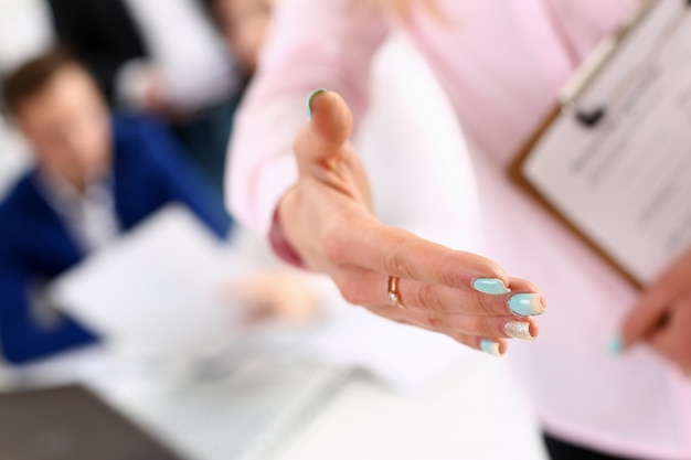 Vrouwelijke beambte die hand voor handdruk uitbreidt