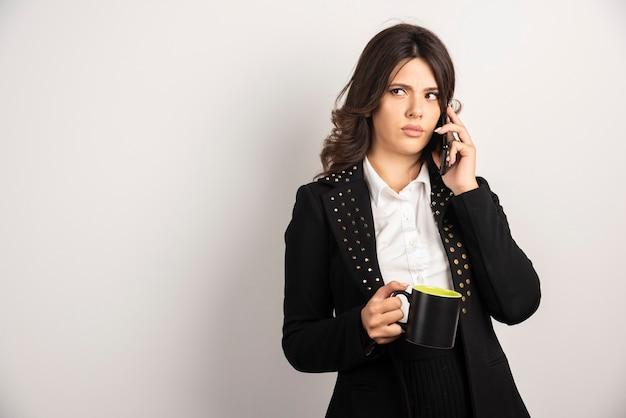 Vrouwelijke beambte die het werk via de telefoon bespreekt