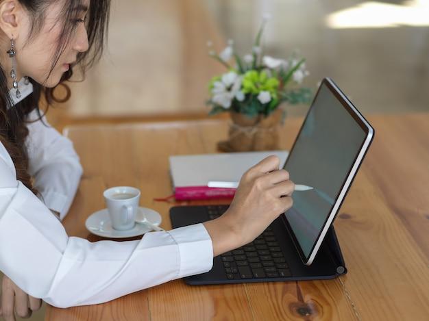 Vrouwelijke beambte die met digitale tablet op houten tafel werkt
