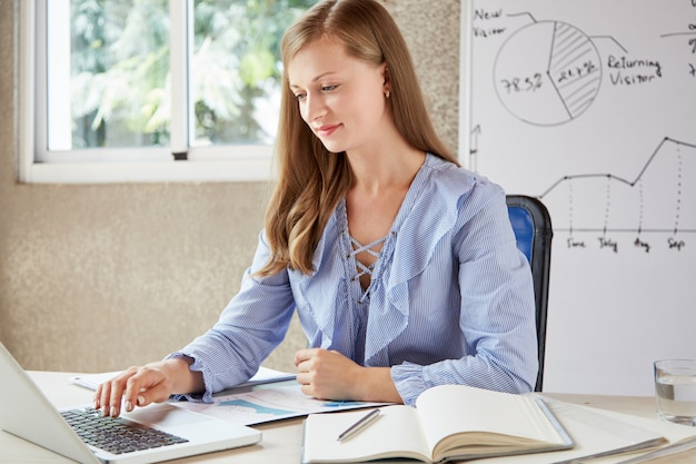 Vrouwelijke beambte die op laptop met een wit bord bij de achtergrond toetst