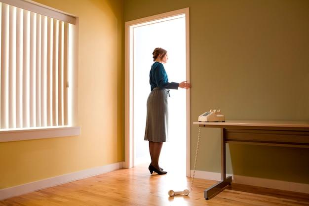 Vrouwelijke beambte die zich in een bureaudeuropening bevindt die een ruimte onderzoekt die met licht wordt verlicht, telefoon verliet de haak