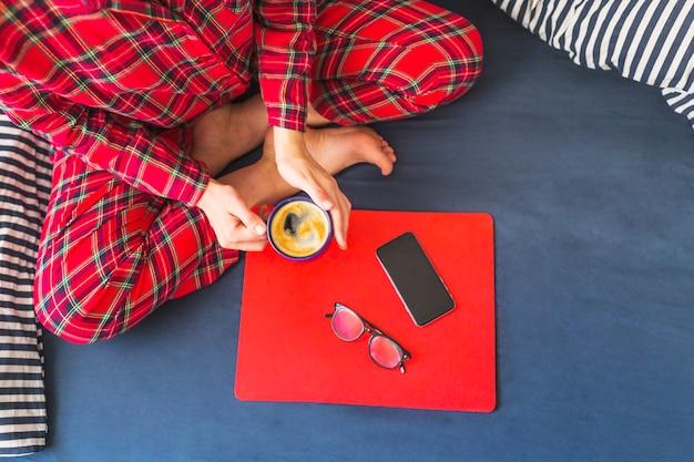 Vrouwelijke bedrijf beker zittend op bed