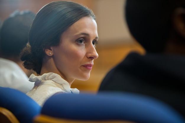 Vrouwelijke bedrijfsleiders luisteren naar toespraak op conferentiecentrum