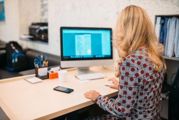 Vrouwelijke bedrijfspersoon zit aan de balie en werkt op de computer op kantoor. secretaris of manager werkplek