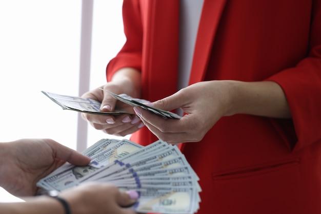 Vrouwelijke bedrijfsvrouw die ons dollarsclose-up samen telt. juridische winst bedrijfsconcept.