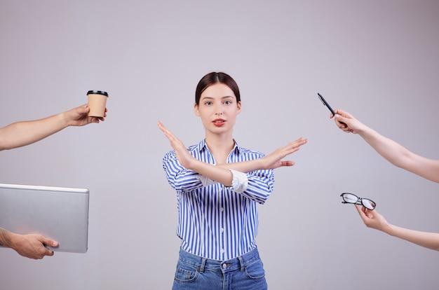 Vrouwelijke beheerder in een gestreept wit-blauw shirt met bril en een laptop op een grijze rug. werknemer van het jaar, zakelijke dame, harde werker.