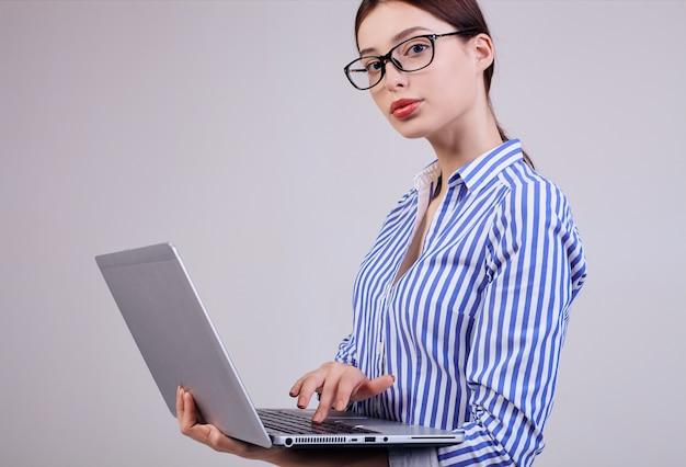 Vrouwelijke beheerder in een gestreept wit-blauw shirt met bril en een laptop op grijs. werknemer van het jaar, zakelijke dame.