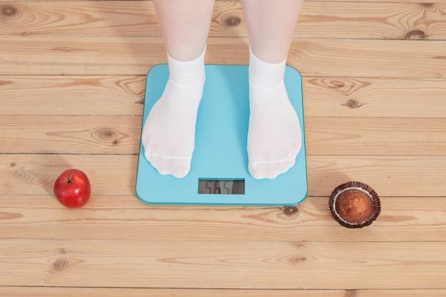 Vrouwelijke benen appel en cake, en elektronische weegschalen op houten vloer