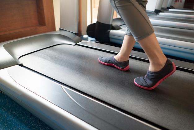 Vrouwelijke benen die en op tredmolen in gymnastiek lopen lopen. cardiotraining trainen