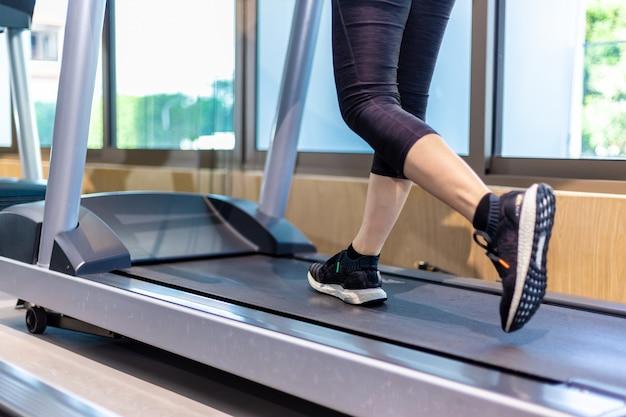 Vrouwelijke benen die op tredmolen bij een gymnastiek lopen