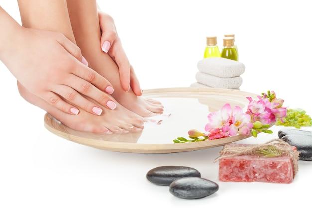 Vrouwelijke benen en handen in de samenstelling van de spabehandeling