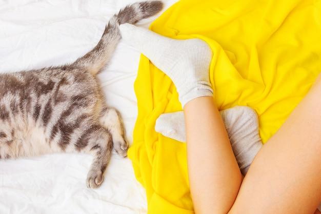 Vrouwelijke benen en kattenvoeten en staart op het gele tapijt.