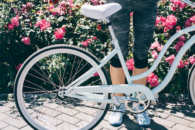 Vrouwelijke benen in blauwe sneakers en een stijlvolle fiets tegen een achtergrond van struiken met rozen